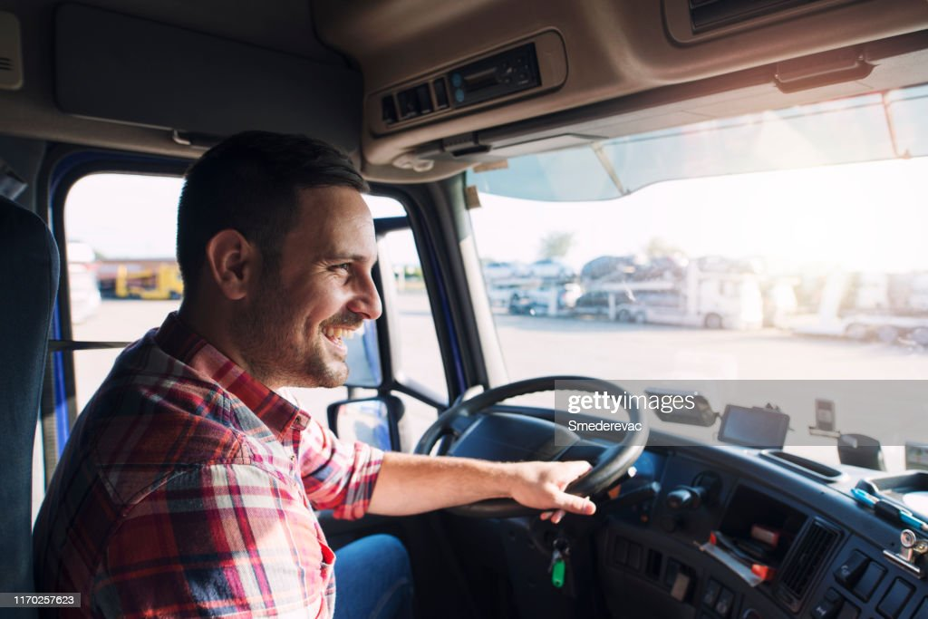 Truck driver job. Middle aged trucker driving truck. : Stock Photo