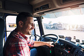 Truck driver job. Middle aged trucker driving truck.
