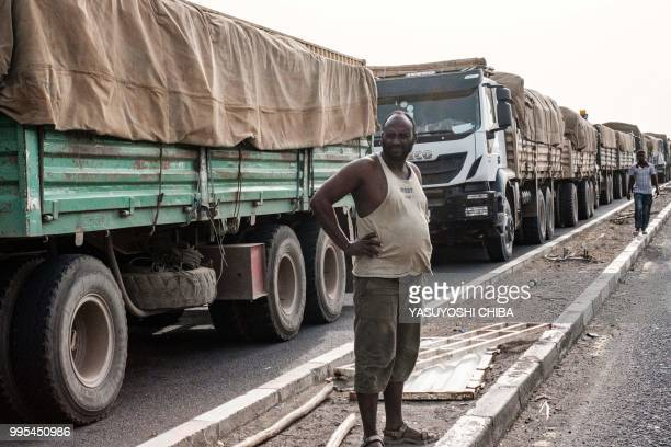 A truck driver poses for a picture as he waits to enter the Doraleh Container Terminal on July 4 2018 in Djibouti East Africa's smallest country...