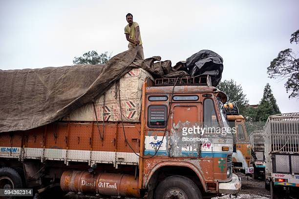 A truck driver removes tarpaulin from the back of a truck at the Bara Bazar market in Shillong Meghalaya India on Tuesday Aug 16 2016 Indian staterun...