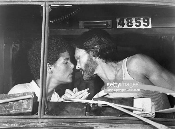 Truck driver Rubber Duck and photojournalist Melissa lean in to kiss in Rubber Duck's cab in a scene from the 1978 film Convoy.