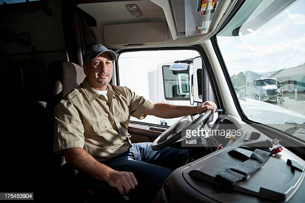 Truck driver sitting in cab of semi-truck