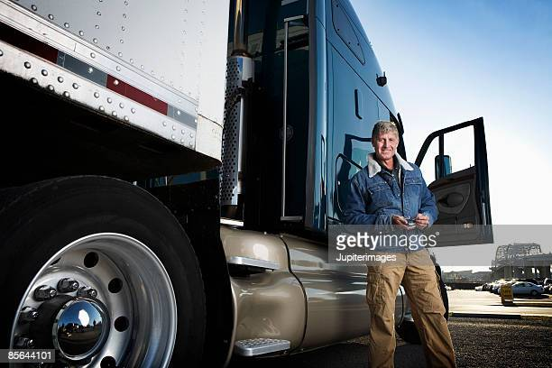 Truck driver standing outside of tractor trailer