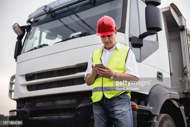 motorista de caminhão, usando um aplicativo móvel - caminhão - fotografias e filmes do acervo