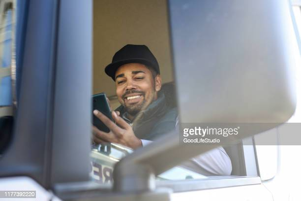 truck driver using a mobile app - truck driver stock pictures, royalty-free photos & images