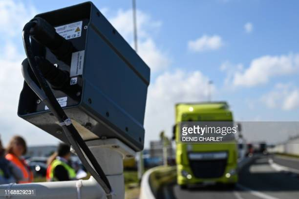 A truck driver waits as a camera checks his plate to determine if his loading will be checked by custom officers during a day of test in case of...