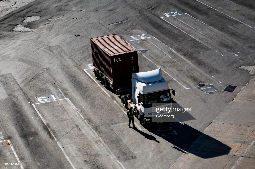 A truck driver waits in a parking zone before moving a small shipping container on the quayside at the commercial port in Barcelona, Spain, on Wednesday, Jan. 29, 2014. Government bonds in Europe's most-indebted countries rallied in the first three weeks of the year on signs the debt crisis that pushed those nations' borrowing costs to euro-era records had abated. Photographer: David Ramos/Bloomberg via Getty Images