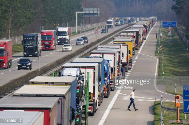 A truck driver walks next to his truck among a line of trucks stretching over 40km on the A12 highway towards Germany's border to Poland on March 17...