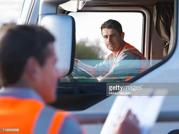 Truck driver with worker taking notes