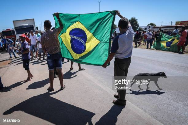 Truck drivers hold Brazilian flags while gathering on BR 040 highway during a protest against rising fuel prices in Luziania Brazil on Wednesday May...
