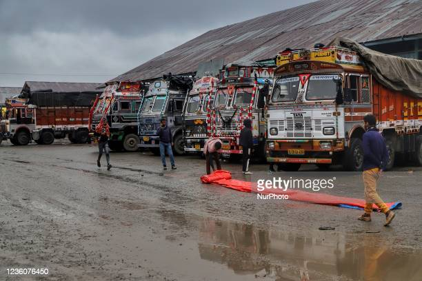 Truck drivers put waterproof on top of the trucks to stop rain from damaging the Apple boxes loaded onto the trucks at Fruit Mandi in Sopore,...