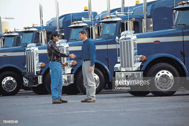 Truck drivers shaking hands in parking lot