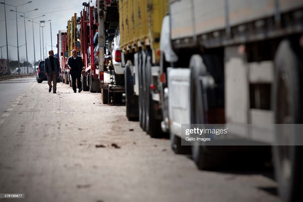 A Truck drivers walking to their trucks on March 12, 2014, in Killis City, Turkey. The truck driver has been at the Kilis border now for 14 days, waiting to go through to the Syrian side. Truck drivers at the Turkish/ Syrian border near Kilis City wait 10-15 days to get their good through to the customs area where Syrian truckers can take the load to Syrian towns. Since ISIS moved out of the nearby Area of Azzaz more goods are collected by the Syrian trucks on the Bab Al Salame border.