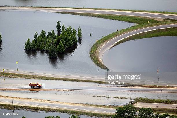 A truck drives along a flooded highway on the Mississippi River on May 23 2011 in Vicksburg Mississippi Floodwaters are beginning to gradually recede...