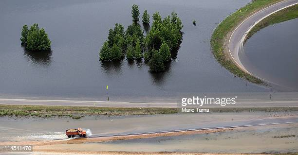 A truck drives along a flooded highway on the Mississippi River floodwaters on May 23 2011 in Vicksburg Mississippi Floodwaters are beginning to...