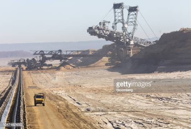 A truck drives alongside a conveyor as a giant excavator and mining machinery operate at the open pit lignite mine operated by RWE AG in Hambach...