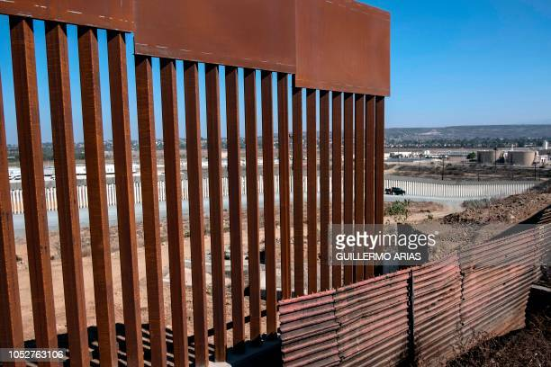 A truck drives near a reinforced section of the USMexico border fence as seen from Tijuana Baja California state Mexico on October 22 2018 US...