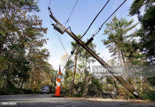 A truck drives near a utility pole propped up by a pine tree limb on High Head Road in Harpswell on Wednesday November 1 2017 Power is still out on...