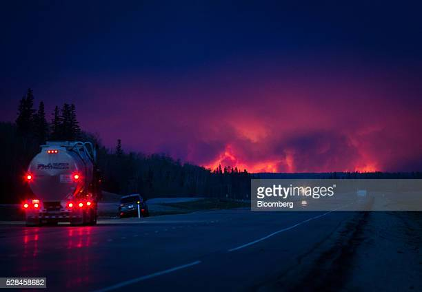 A truck drives on a highway as a wildfire burns south of Fort McMurray Alberta Canada on Wednesday May 4 2016 A fire fueled by shifting winds that...