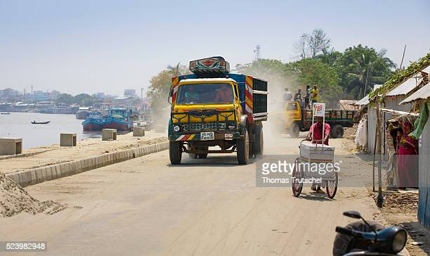 A Truck drives on a newly built Town Protection Embankment which serves to protect the adjacent residential area on April 11 2016 in Khulna Bangladesh