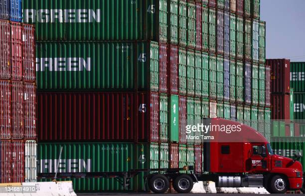 Truck drives past cargo containers stacked at the Port of Los Angeles, the nation's busiest container port, on October 15, 2021 in San Pedro,...