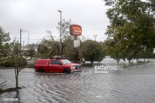 A truck drives through a flooded parking lot after Hurricane Florence in Wilmington North Carolina US on Saturday Sept 15 2018 Florences plodding...