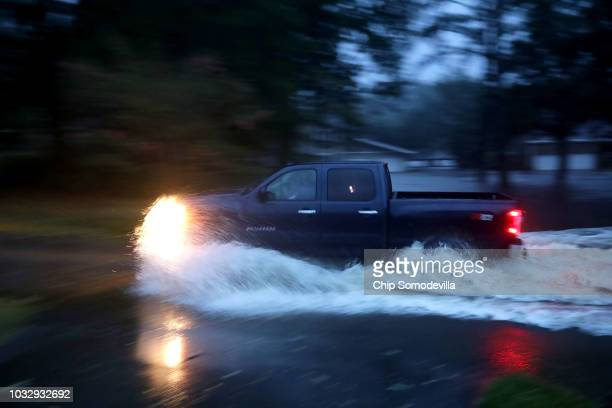 A truck drives through deep water after the Neuse River went over its banks and flooded the street during Hurricane Florence September 13 2018 in...