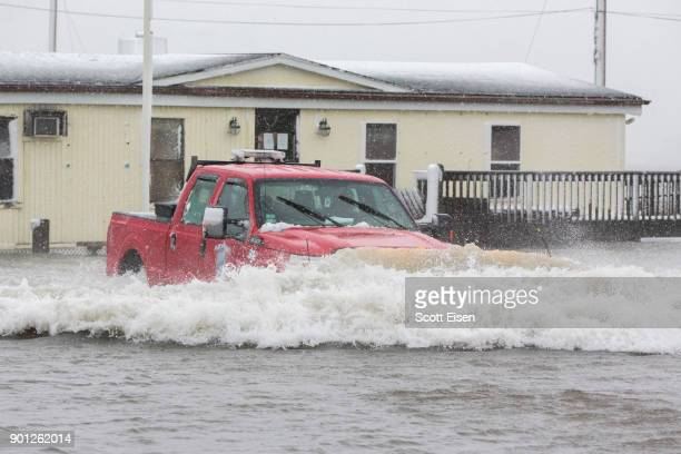 A truck drives through flood waters while a massive winter storm bears down on the region on January 4 2018 in Marshfield Massachusetts The 'bomb...