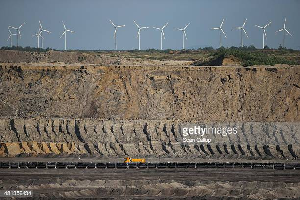 A truck drives through the Welzow Sued openpit lignite coal mine as wind turbines spin nearby on July 9 2015 near Welzow Germany The Welzow Sued mine...