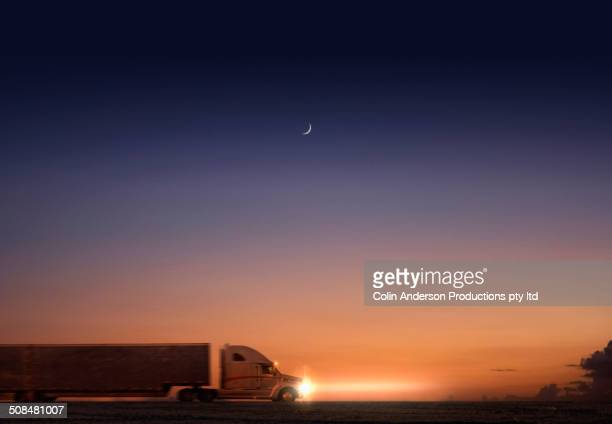 Truck driving at sunset