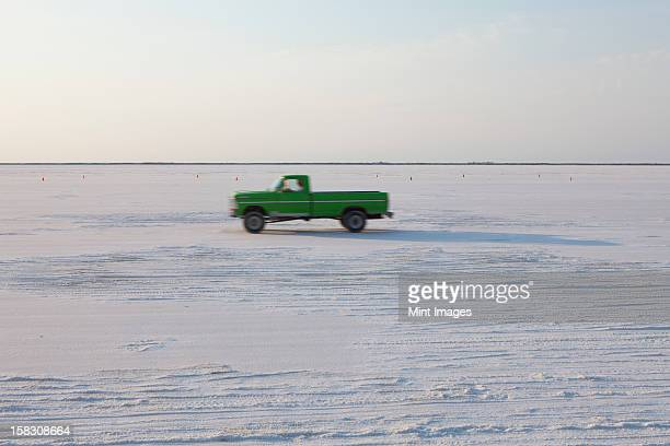 truck driving on bonneville salt flats, during speed week, dusk - bonneville salt flats stock photos and pictures