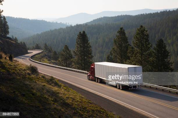 truck driving on remote highway - trucking stock pictures, royalty-free photos & images