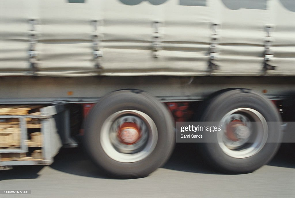 Truck driving on road, section (blurred motion) : Stock Photo