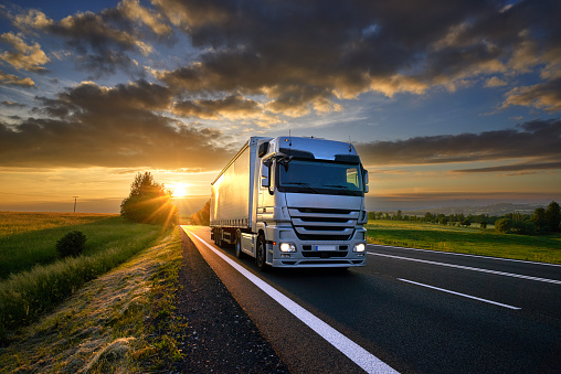 Truck driving on the asphalt road in rural landscape at sunset with dark clouds 859916128
