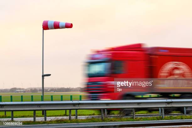 Truck driving past a windsock on a highway