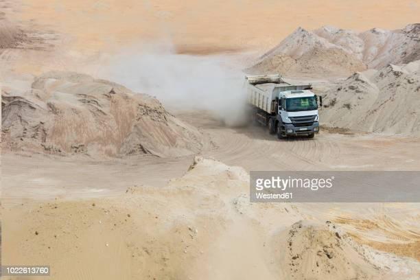 truck driving through sand heaps - ダンプカー ストックフォトと画像