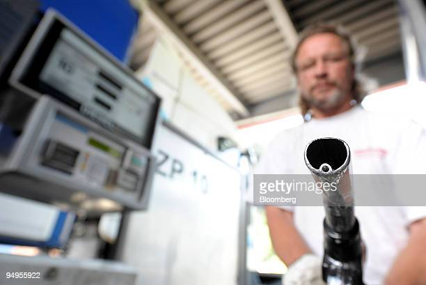 A truck drvier holds a fuel nozzle at a gas station in Kufstein Austria on Monday May 18 2009 Demand for distillate fuel which includes diesel and...