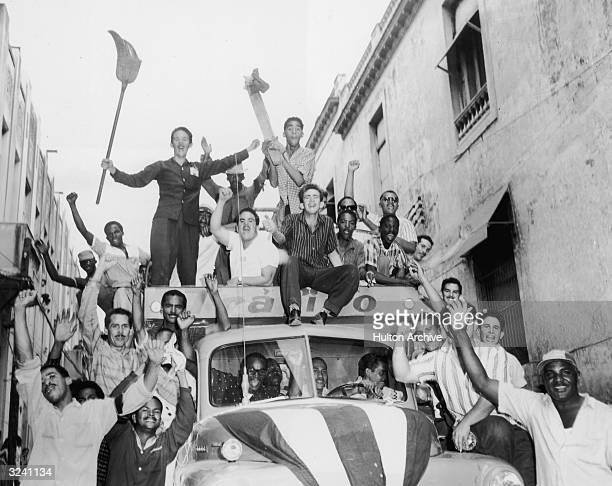 A truck filled with Cuban men rides through a narrow Havana street after the triumph of the Cuban Revolution and the overthrow of former dictator...