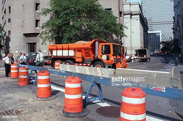 A truck filled with sand and cement blocks is part of security measures to close off a street leading to the Federal Courthouse and jail 28 August in...