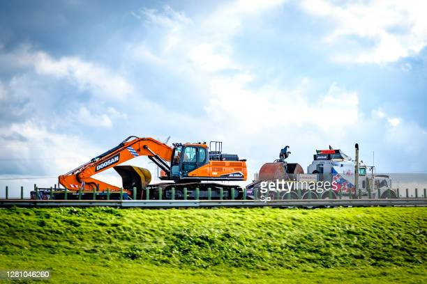 "truck hauling a trailer with an excavator driving on a highway - ""sjoerd van der wal"" or ""sjo"" stock pictures, royalty-free photos & images"