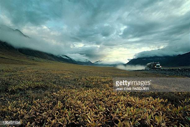 Truck in Alaskan landscape in United States crossing Brooks range on his way to the oil fields of Prudhoe Bay