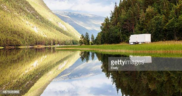 Truck in landscape  reflected  in the clear waters at sunset.