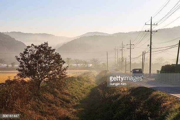 a truck is driving along farm road - sungjin kim stock pictures, royalty-free photos & images