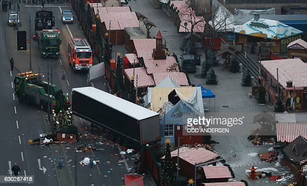 TOPSHOT A truck is towed away on December 20 2016 as forensic experts examine the scene around a truck that crashed into a Christmas market near the...