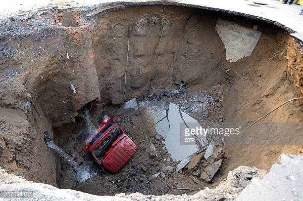A truck lies in a sinkhole which occured overnight on Shiliuzhuang road in Beijing on April 26 2011 A section of the road collapsed beneath a truck...