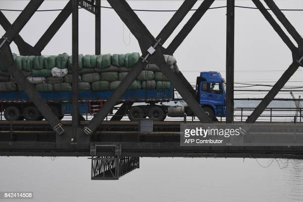 A truck loaded with goods makes its way across the Friendship Bridge from the Chinese border city of Dandong in China's northeast Liaoning province...