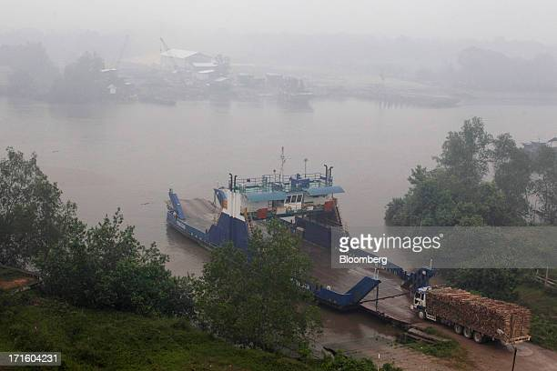 A truck loaded with logs drives onto a ferry as haze surrounds the area in Siak Riau Province Indonesia on Wednesday June 26 2013 Indonesia is open...
