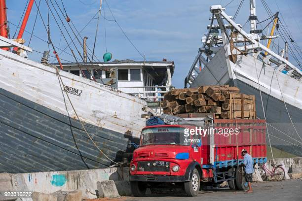 Truck loaded with timber in front of wooden pinisis phinisis traditional Indonesian cargo ships in the harbour of Semarang Central Java Indonesia