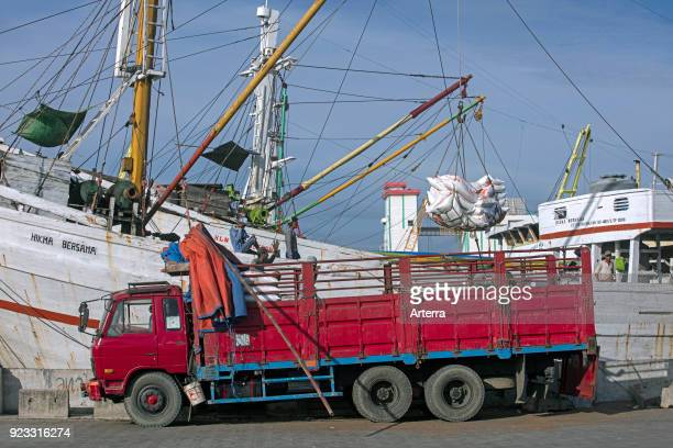 Truck loading merchandise from wooden pinisi phinisi traditional Indonesian cargo ship in the harbour of Semarang Central Java Indonesia