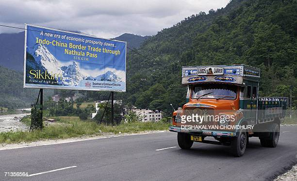 A truck makes its way through the hill tracks past a billboard on the proposed reopening of the Nathu La Pass the IndiaChina border between India's...